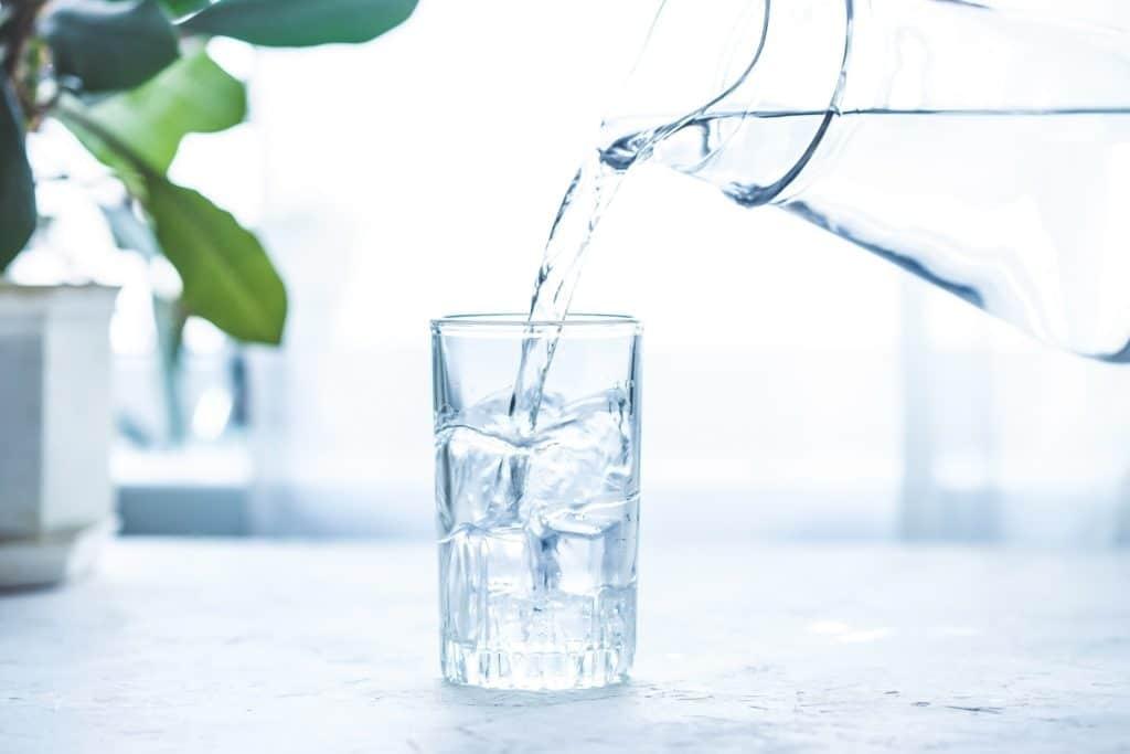 Wasser wird aus Krug in Glas mit Eiswürfeln gegossen