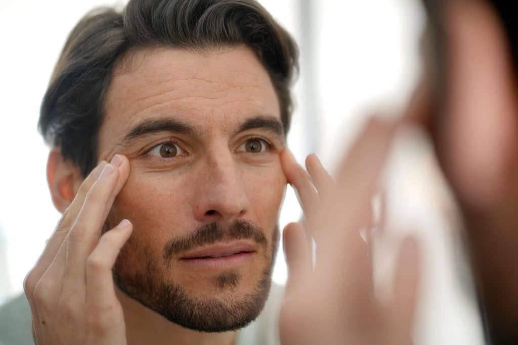 Mann mustert seine Augenfalten im Spiegel