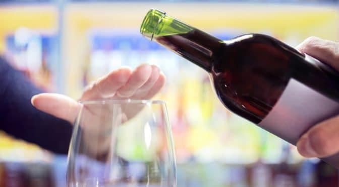 Frau lehnt Glas Wein ab