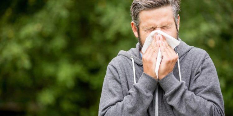 Mann niest in ein Taschentuch.