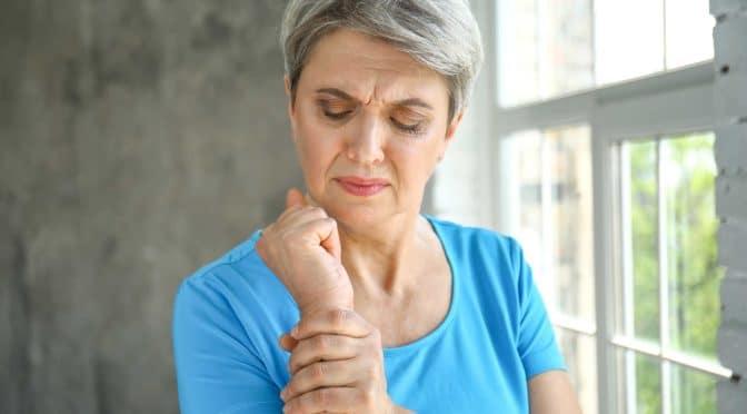 Frau hält schmerzendes Handgelenk
