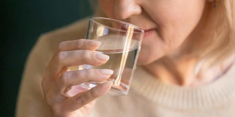 Eine Frau trinkt Wasser aus einem Glas.
