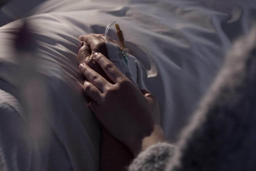 Hände halten am Krankenbett