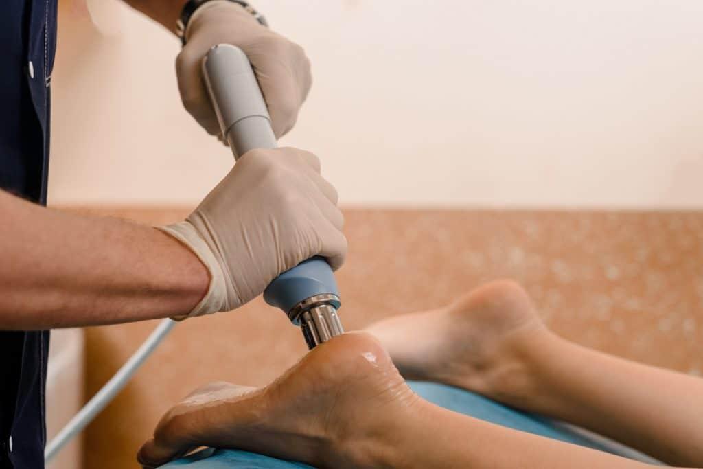 Therapeut führt Stoßwellentherapie am Hacken eines Patienten durch.