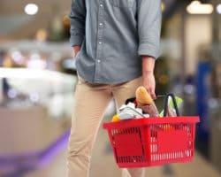 Mann mit gefülltem Einkaufskorb im Supermarkt