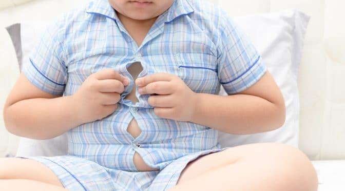 Übergewichtiger Junge versucht sein Hemd zuzuknöpfen.