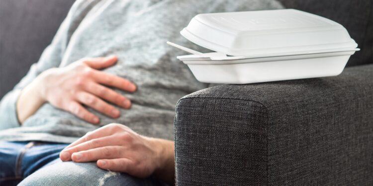 Ein Mann sitzt auf einem Sofa und hält sich eine Hand auf den Bauch.