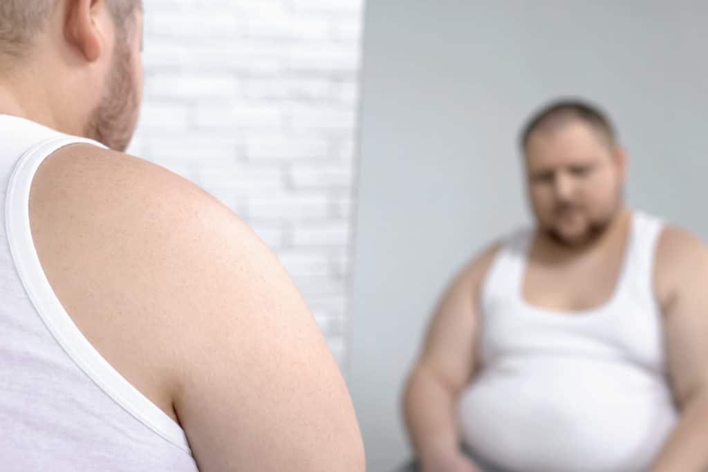 Übergewichtiger Mann vor dem Spiegel