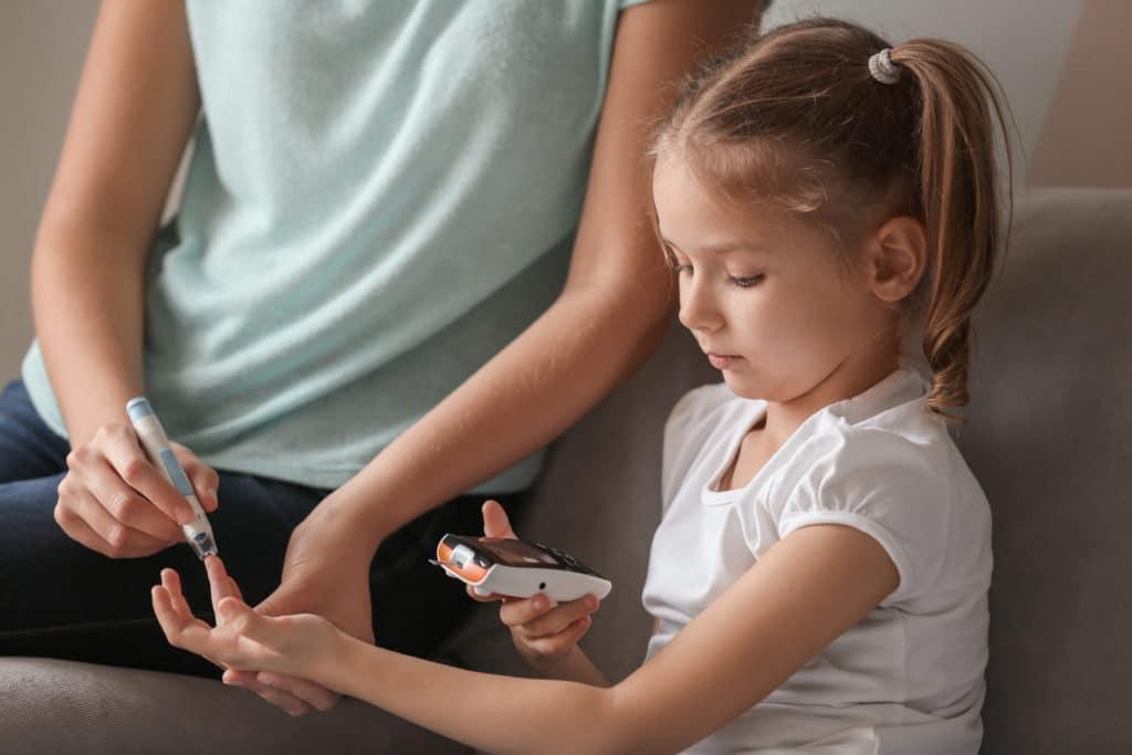 Mutter nimmt von ihrer zuckerkranken Tochter eine Blutprobe mit einem Insulin-Pen