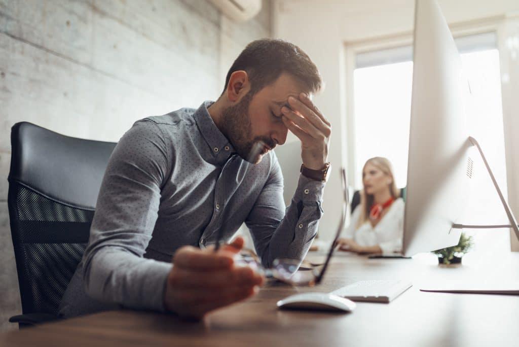 Mann sitzt vorm PC am Schreibtisch und hält sich die Stirn.