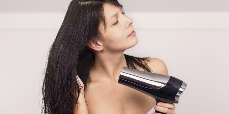Eine Frau mit umgewickeltem Handtuch föhnt sich im Badezimmer die Haare