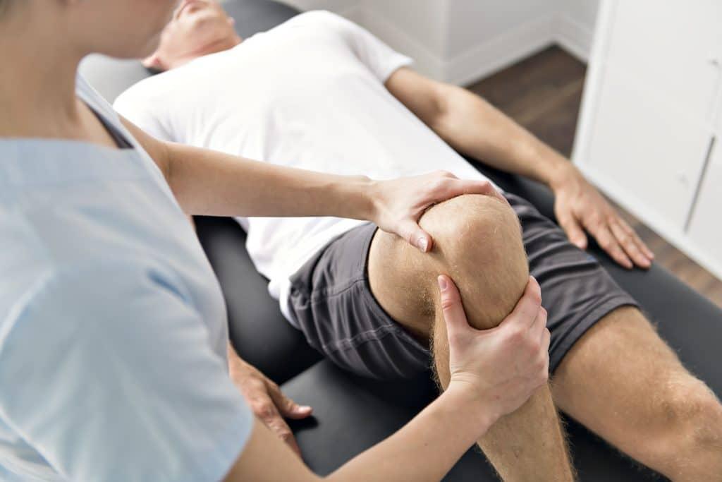Mann während  Physiotherapie am Knie