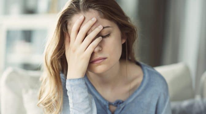 Eine junge Frau leidet unter starken Kopfschmerzen.