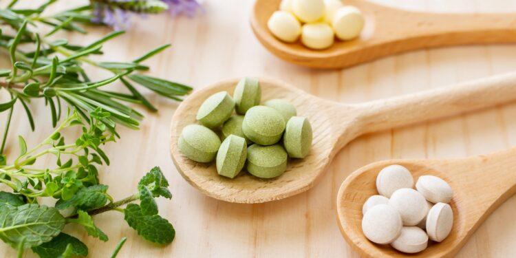 Weiße, grüne und gelbe Tabletten auf Holzlöffeln neben Kräuterzweigen