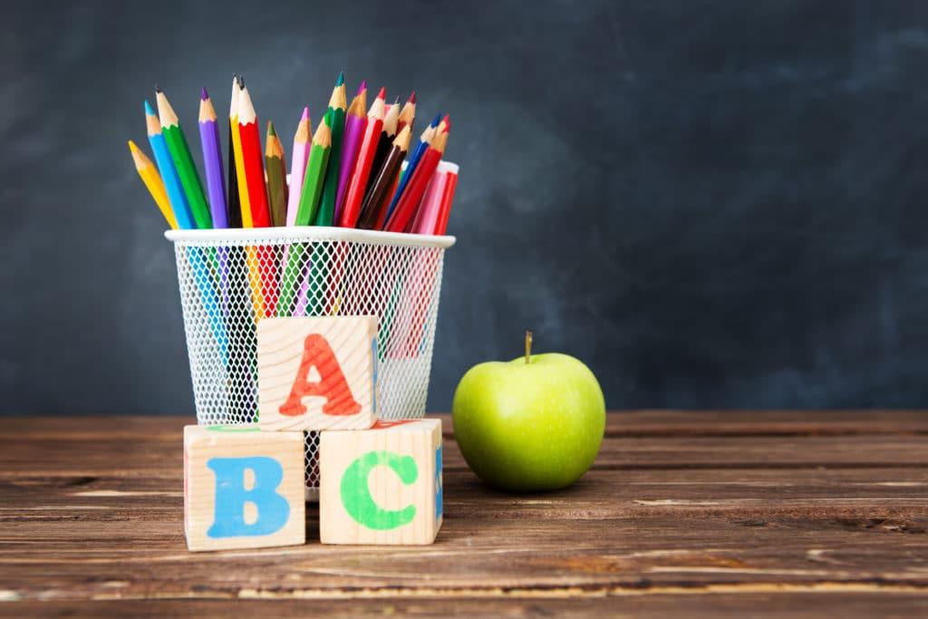 Ein Korb voller Buntstifte mit einem Apfel daneben
