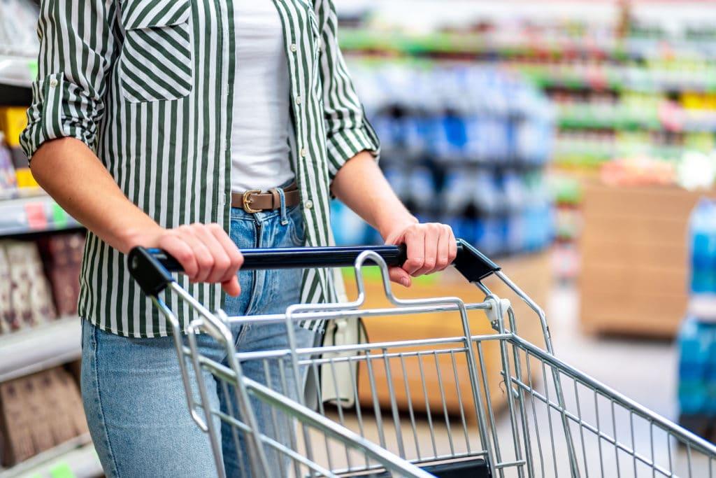 Frau schiebt Einkaufswagen im Supermarkt