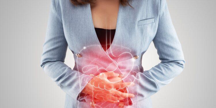 Eine Frau mit Schmerzen im Magen-Darm-Bereich hält sich die Arme vor den Bauch.