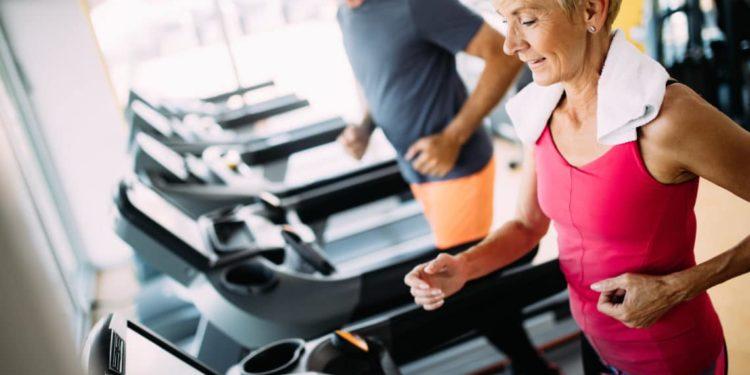 Zwei ältere Menschen laufen auf einem Laufband im Fitnesscenter