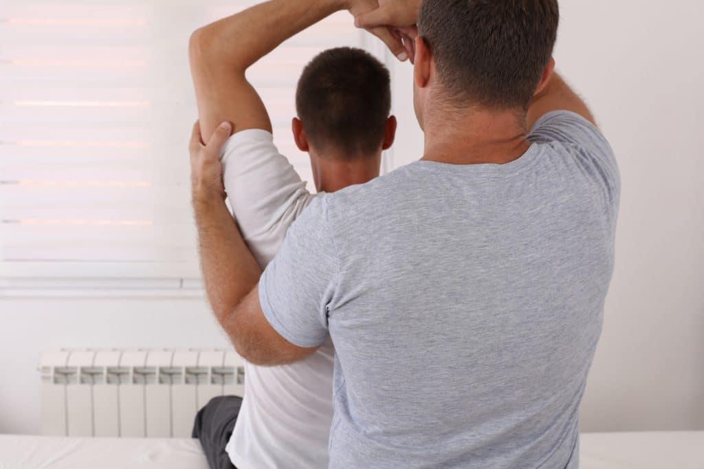 Therapeut dehnt linken Arm eines Patienten.