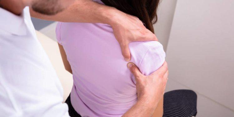 Behandler drückt mit den Daumen einen Punkt in Schulternähe der Patientin.