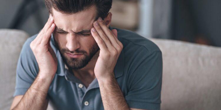 Mann in blauem Poloshirt massiert mit den Fingerspitzen beide Schläfen und verzieht das Gesicht vor Schmerzen