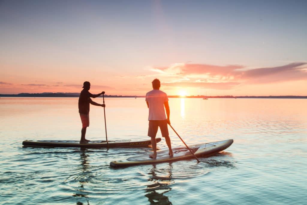 Zwei Männer beim Stand-up-paddling auf einem See