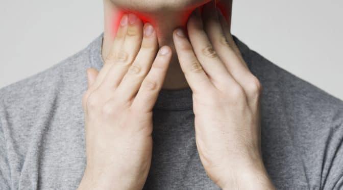 Mann zeigt auf Schmerzen im Hals