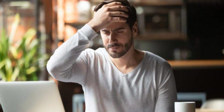 Ein Mann sitzt vor einem Computer und fasst sich an die Stirn.