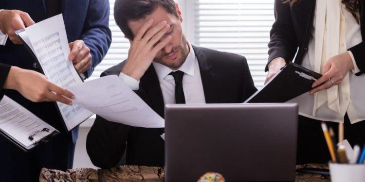 Mann sitzt gestresst im Büro umkreist von Mitarbeitenden.
