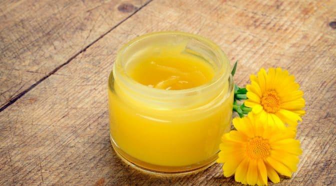 Gelbe Salbe in durchsichtigem Tiegel und zwei Ringelblumen auf einem Holztisch.