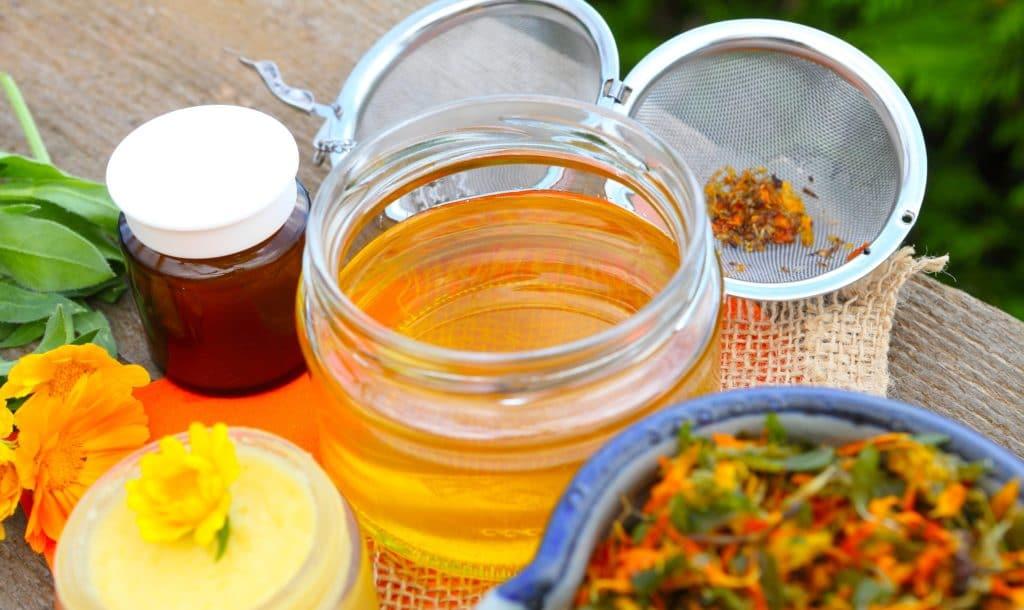 Öl, Ringelblüten, Sieb, ein Cremetiegel und ein Braunglas-Tiegel auf einem Tisch.