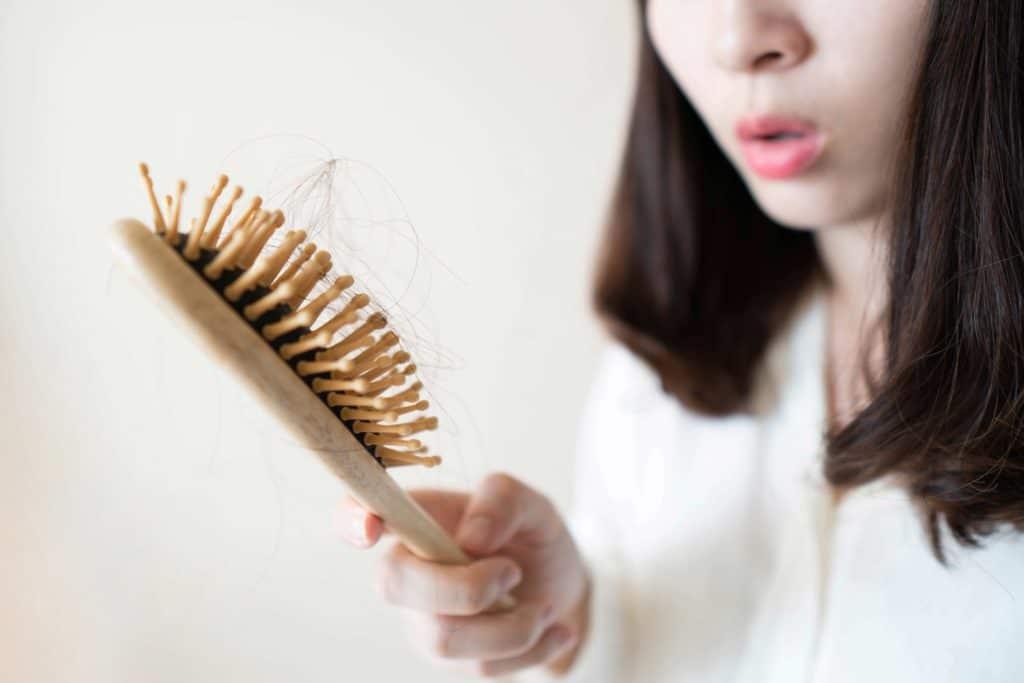 Frau guckt die Haarbürste an