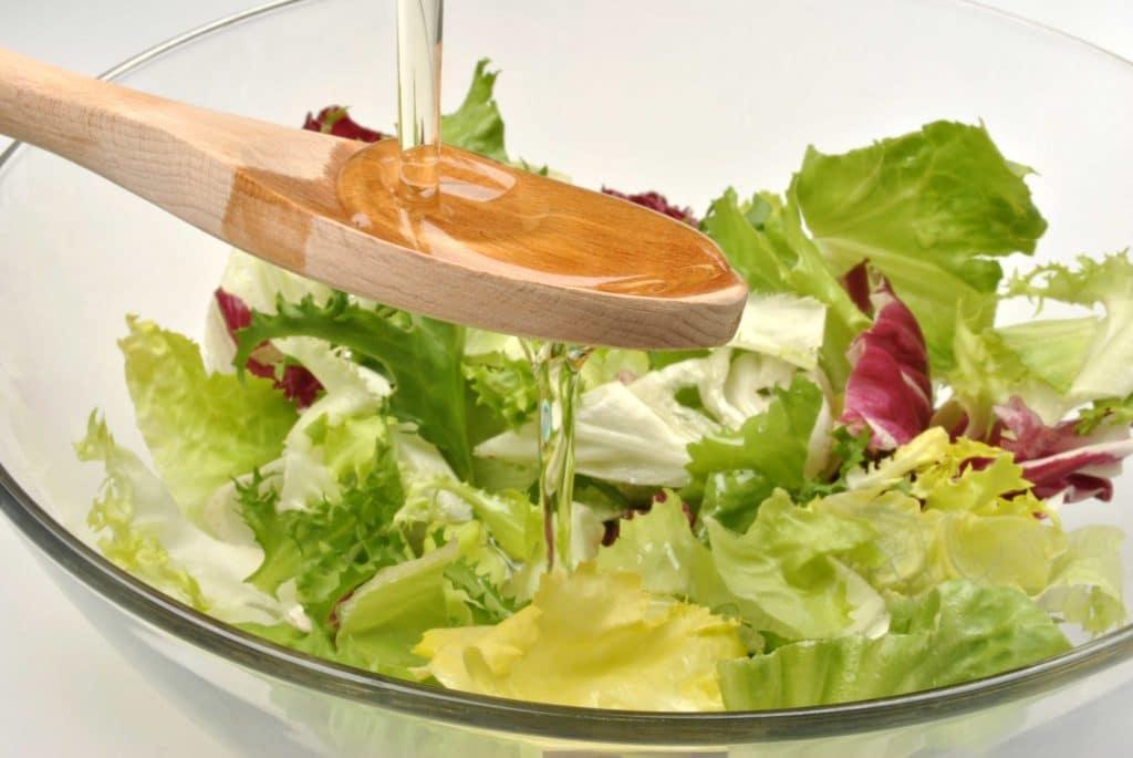 Öl wird über Salat gegossen