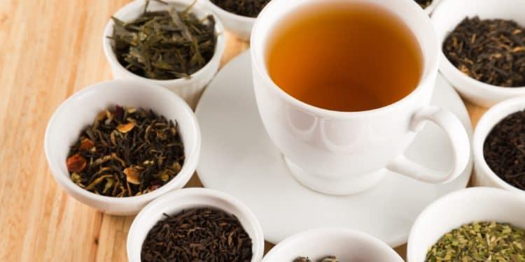 Auf einem Tisch stehen eine Tasse Tee und mehrere kleine Schälchen mit verschiedenen Teekräutern.