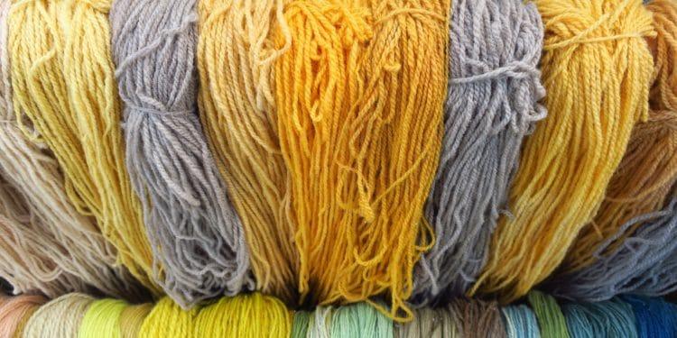 Bunt gefärbte Wolle nebeneinander aufgehängt.