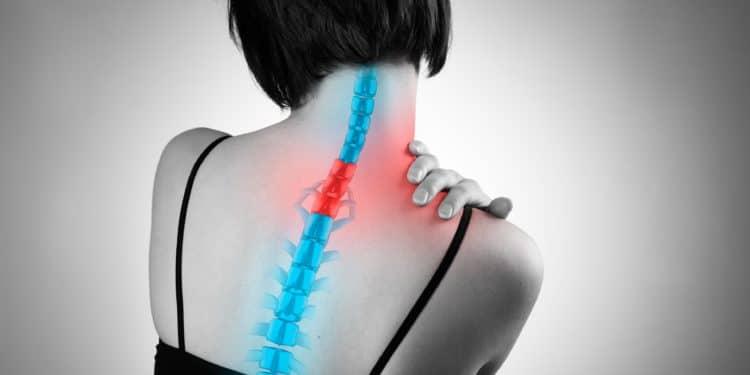 Eine Frau hat Schmerzen in der Halswirbelsäule und berührt mit der Hand den betroffenen Bereich am oberen Rücken.