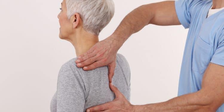 Ein Chiropraktiker tastet die Wirbelsäule einer Patientin ab.