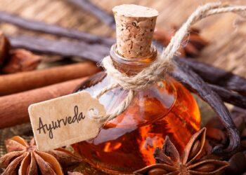 Fläschchen mit Öl mit Beschriftung Ayurveda, daneben Zimtsterne und Zimtstangen