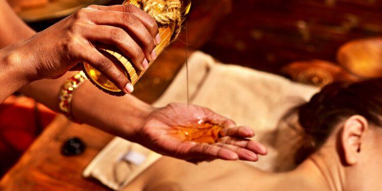 Masseurin gießt sich Öl aus einer Glasflasche in die Hand