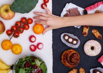 Verschiedene Lebensmittel auf weißem und schwarzem Untergrund und eine Hand, die eine Mandarine greift