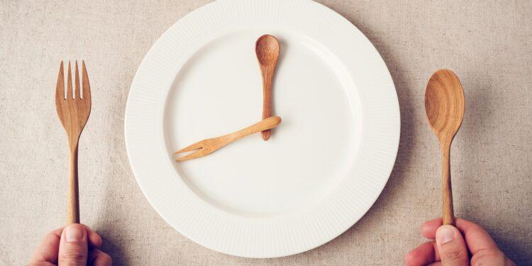 Leerer Teller mit Holzbesteck, das wie zwei Zeiger einer Uhr auf dem Teller liegt, daneben zwei Hände, die Messer und Löffel aus Holz halten