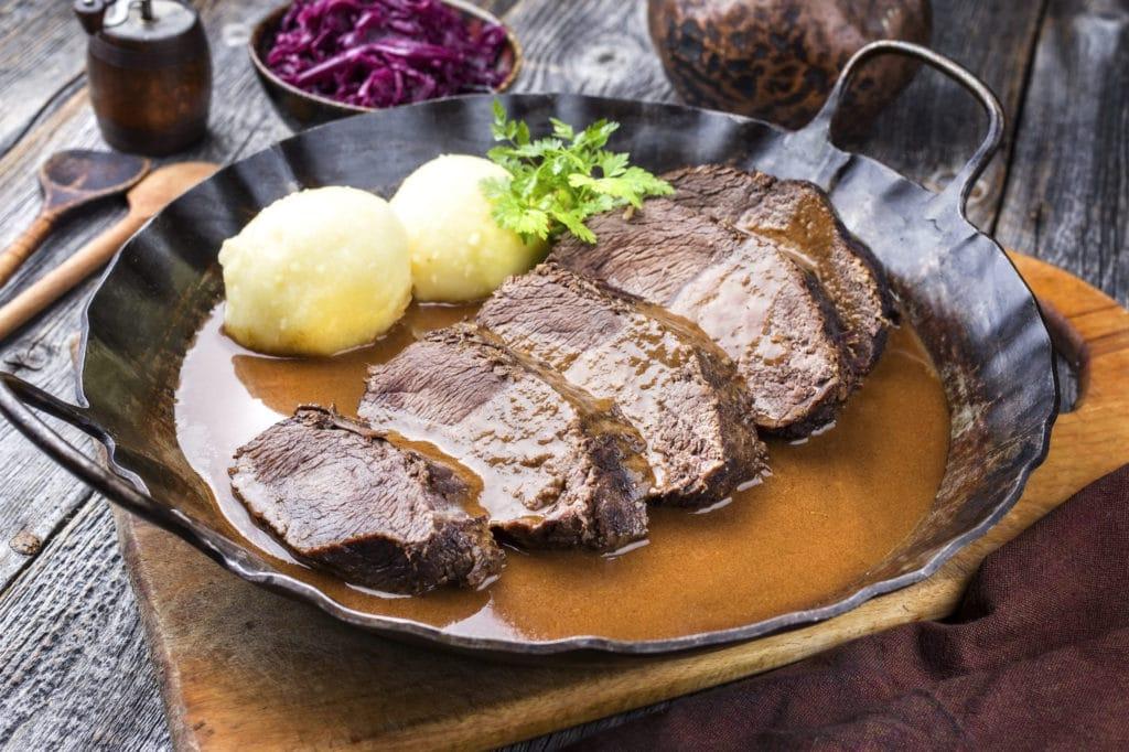Sauerbraten und Kartoffelknödel in einer Pfanne mit Sauce