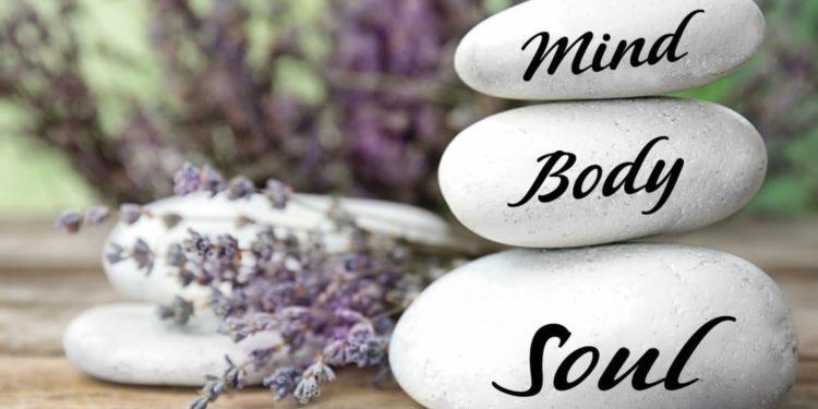 Drei aufeinander gestapelte Steine auf denen die Elemente des Ganzheitsprinzips, Körper, Geist und Seele, geschrieben steht.