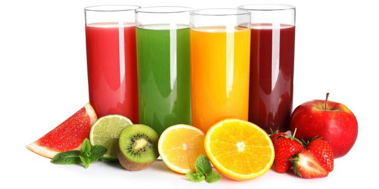 Verschiedene Fruchtsäfte in Gläsern mit einigen Obststücken als Deko am Fuß der Gläser