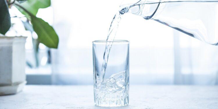 Aus einer gläsernen Wasserkaraffe fließt klares Wasser in ein Glas
