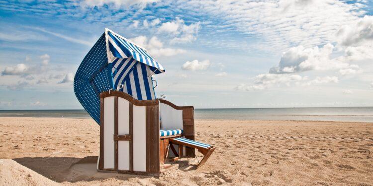 Blau und weiß gestreifter Strandkorb im Sand vor einer Kulisse von Meer und Himmel