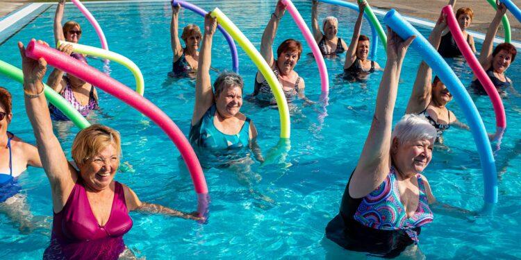Gruppe fröhlicher Seniorinnen bei der Wassergymnastik mit Poolnudeln