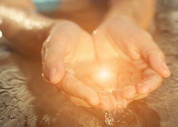 Mit Wasser gefüllte, von der Sonne beschienene Hände