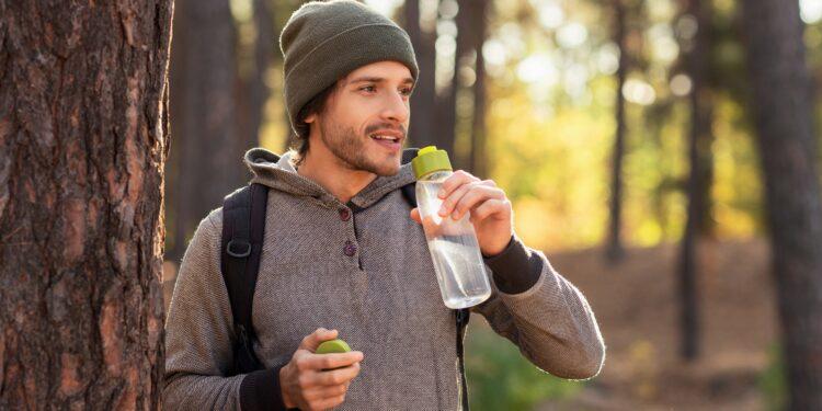 Mann mit Mütze und Rucksack im Wald hält eine Trinkflasche mit Wasser in der Hand