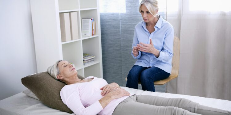 Hypnotisierte Frau liegt auf der Couch in der Praxis einer Therapeutin